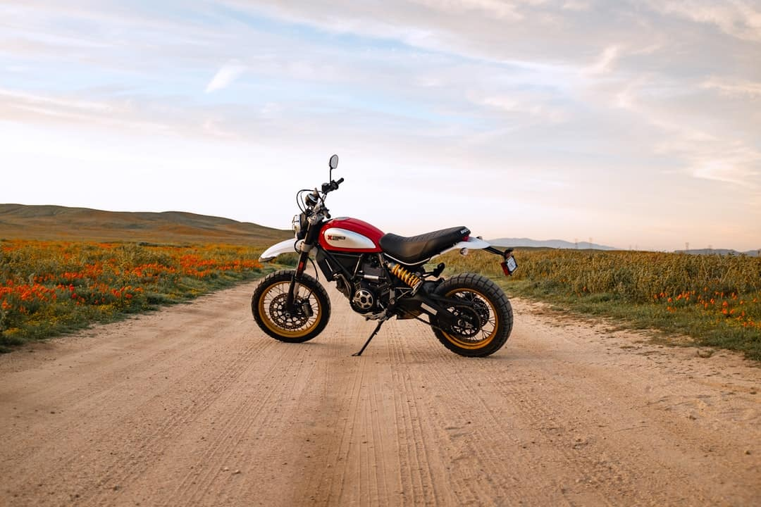 A motorcycle parked on the side of a dirt road