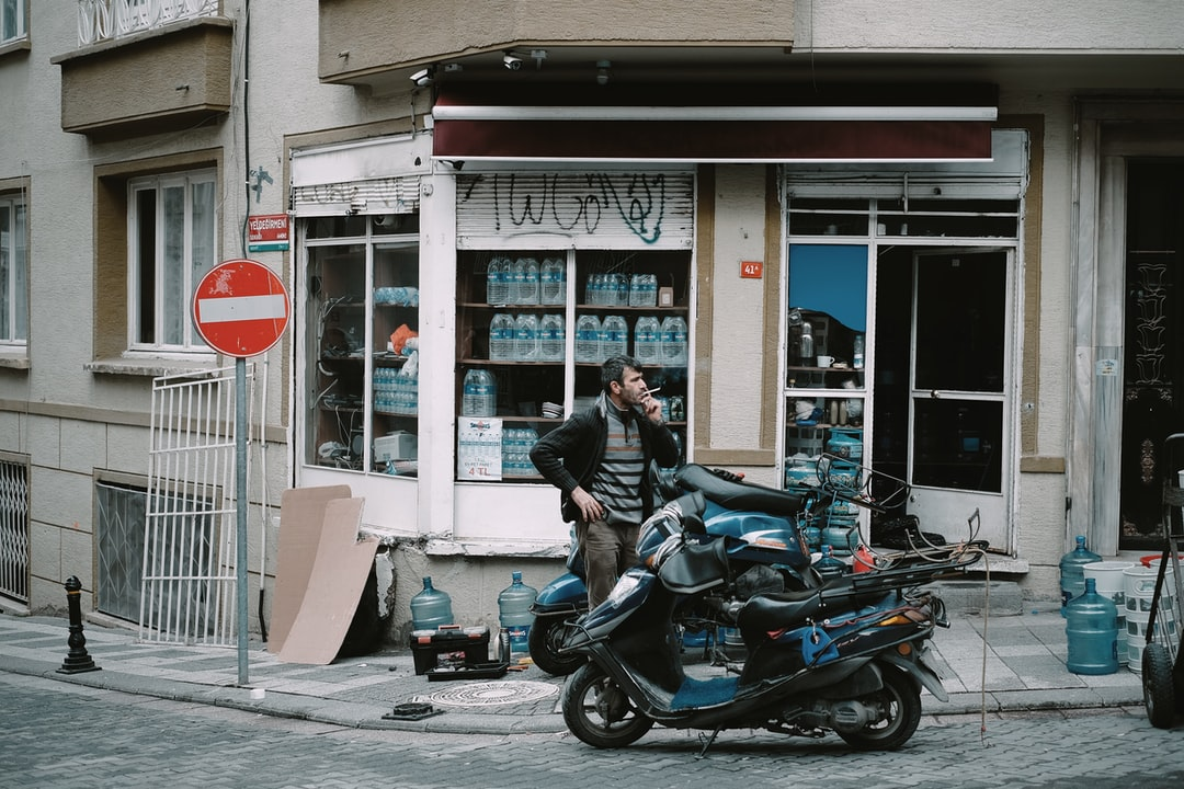 A person riding a motorcycle down a street in front of a building